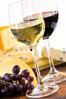 Две чаш с бяло и червено вино до тях жълт кашкавал