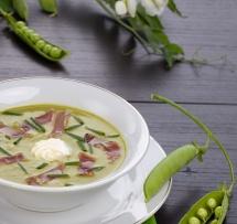 Гъста бяла  бобена супа с  червени резени в бяла купичка