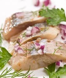Парчета риба херинга с подправки върху бяла чиния