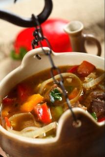 Глинен гърне с зеленчуци и месо на сиво червен фон