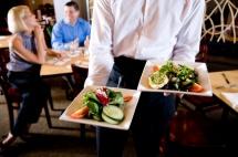 Сервитьор носи храна в бели чинии в ресторант