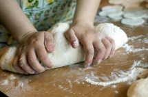 Жена меси с ръце бяло тесто върху маса