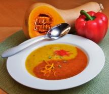 жълто-червена крем супа с фиде в бяла купичка