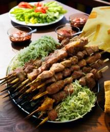 Свински шишчита в чиния със салато от зеле