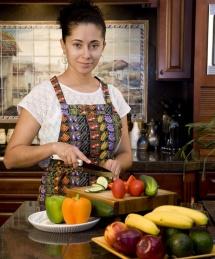 Домакиня реже плодове и зеленчуци на дървена дъска в кухня