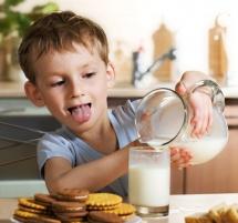 Момче налива от кана с мляко в чаша