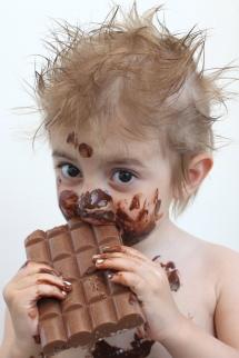 Малко дете оцапано  по цялото лице с разтопен шоколад на бял фон