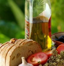 Бутилка зехтин, домат и чесън и филии хляб на зелен фон