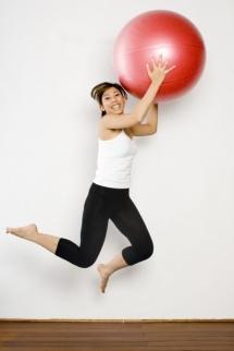 Жена с червена топка фитбол подскача