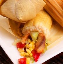 Ястие в царевчно листо със зърна царевица върху маса