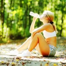 Момиче което пие вода в гора и седи на земята