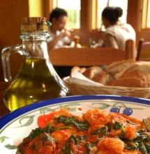 Бутилка зехтин и чиния с червено ястие в ресторант