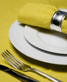 изгладена зелена покривка с прибори и бяла чиния