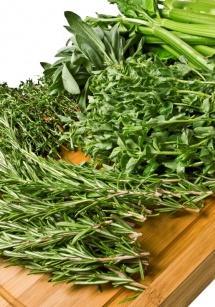 Куп зелени билки на дървена дъска на бял фон