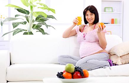 Бременна жена с чаша поркокалов сок и седи на диван