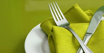 зелена покривка в бяла чиния с вилица и нож на зелен фон
