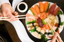 чиния пълна с различни видове суши и две ръце с китайски клечки