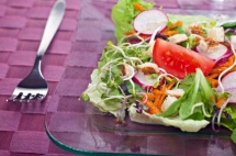Салата с кълнове върху чинийка на лилава покривка