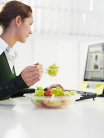 млада дама хапва зелена салата пред компютъра си