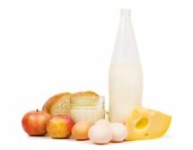 Бутилка мляко,  жълт кашкавал  и бели яйца на бял фон