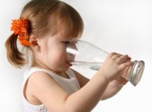 момиченце с бял потник пие вода от стъклена чаша