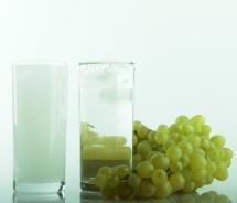 Чаша с прозрачна течност - ракия и  грозд върху маса