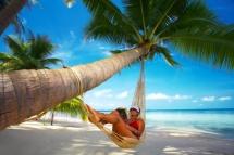 на плажа момиче в хамак спи под палмата