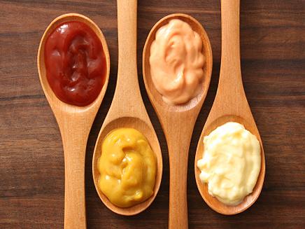 различни на цвят сосове в дървени лъжици