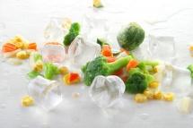 Кубчета лед и зелени броколи и царевица върху бял фон