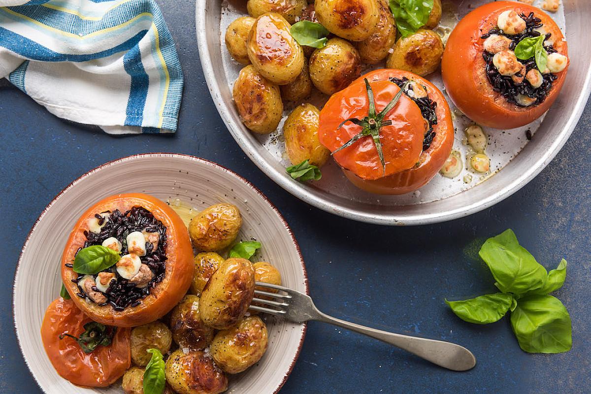Pomodori ripieni di riso nero e formaggio con patate novelle al forno