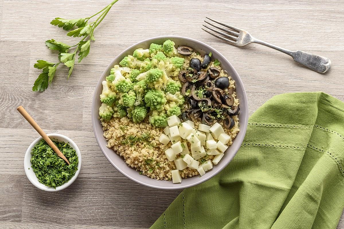 Cous cous integrale con broccolo romanesco, olive nere e caciottina