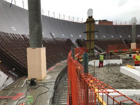 In de kom! Met een beeld van de enorme kolommen die de vloer(en) gaan dragen. Op de voorgrond het aanhechtings staal tussen de funderingsbalk en de nog te storten begane grond vloer. Rode hekwerk is valbeveiliging.