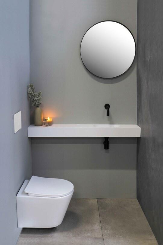 Strakke toiletruimte met fonteinset en ronde spiegel