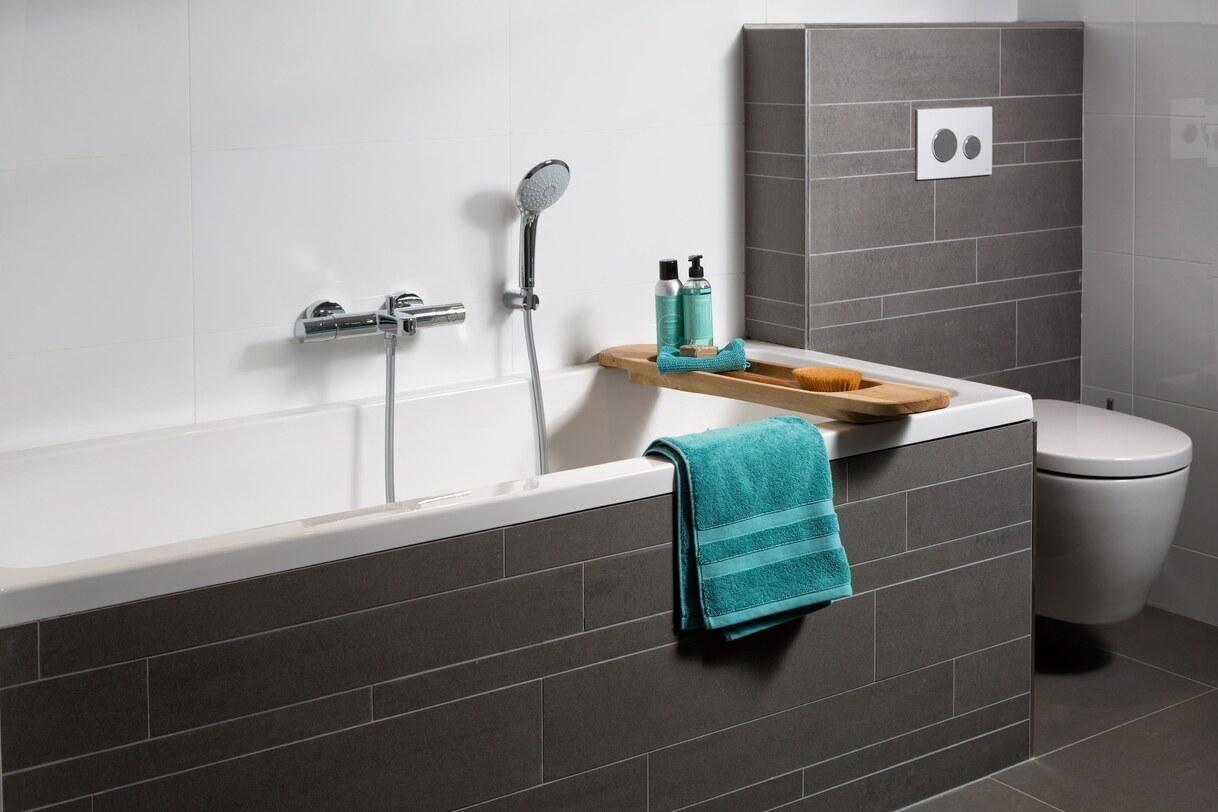 Betegelde voorzetwand toilet en inbouwbad met grijze tegelstroken