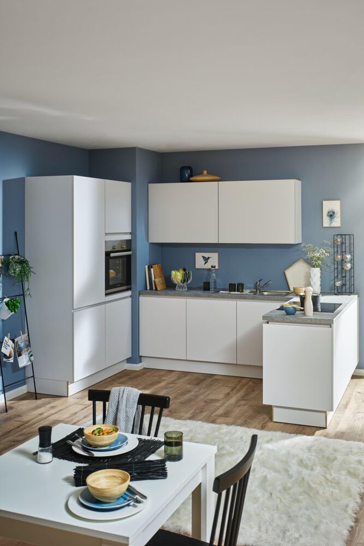 Strakke greeploze witte keuken met bovenkasten
