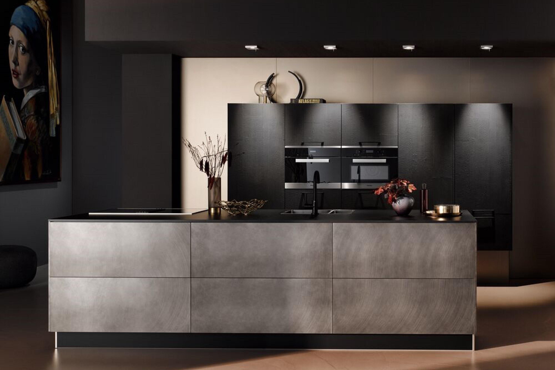 Stoere RVS keuken met robuuste zwarte hoge kastenwand
