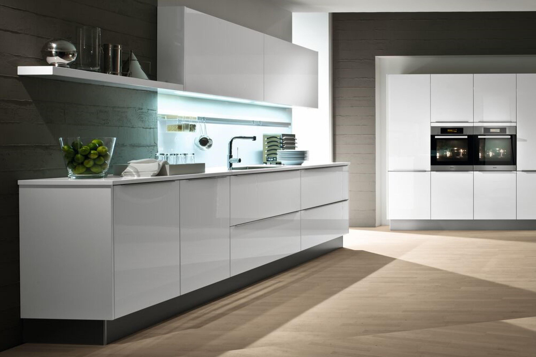Hoogglans witte keuken met hoge kastenwand
