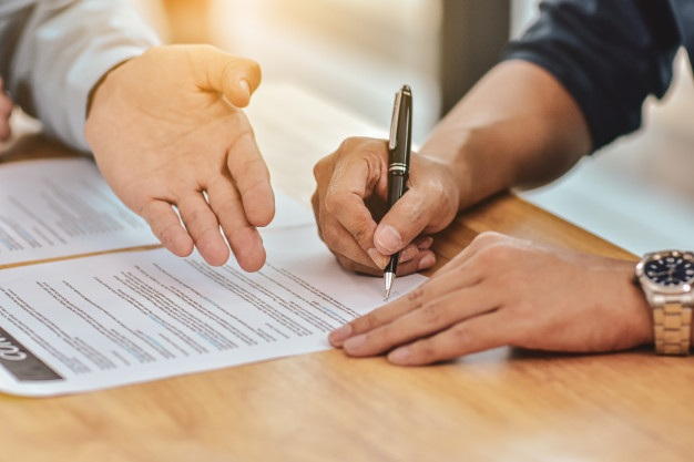 Close up hand holding pen sign contract document 10541 1024