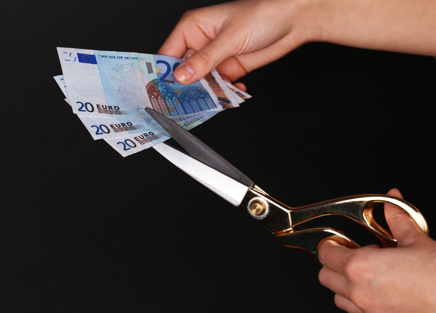 Hands with scissors cutting euro banknotes black space