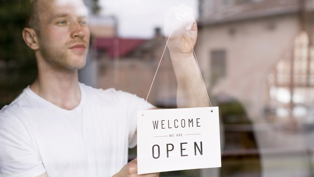 Male waiter putting welcome sign coffee shop window 23 2148581180