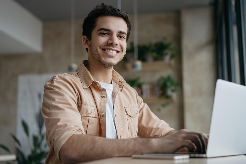Smiling freelancer copywriter using laptop working from home