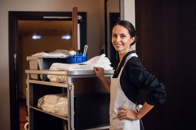 Smiling hotel maid with fresh towels doing housekeeping 225094 136
