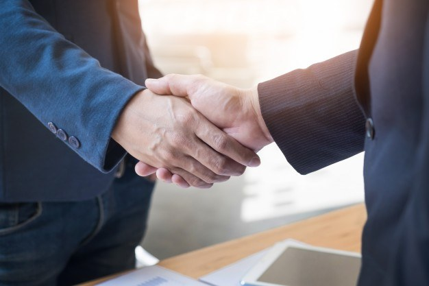 Two confident business man shaking hands during meeting offi