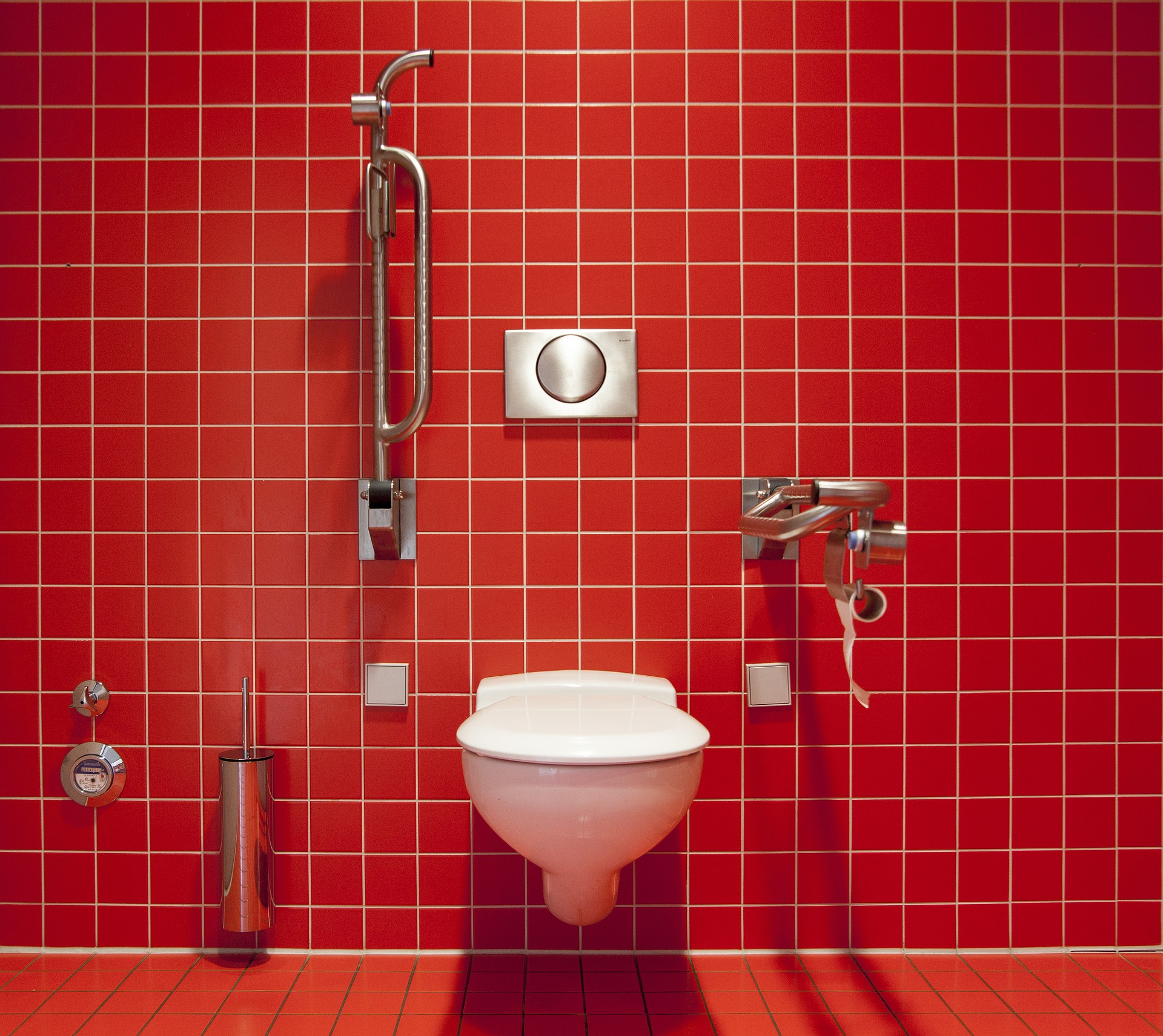 Lovely toilet fitted with red tiled background not likely to become clogged for a while due to modern fittings.