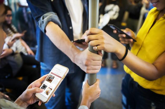Adult-using-phones-in-metro