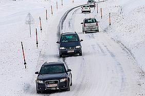 Mehrere Pkw unterwegs auf verschneiter Gebirgsstraße