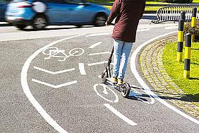 E-Tretrollerfahrerin auf einem Radweg unterwegs