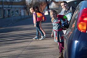 Kinder überqueren zwischen Autos eine Straße