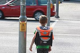 Kind steht auf dem Schulweg an einer Ampel.