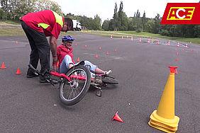 Trainer hilft gestürzter Pedelec-Fahrerin auf.